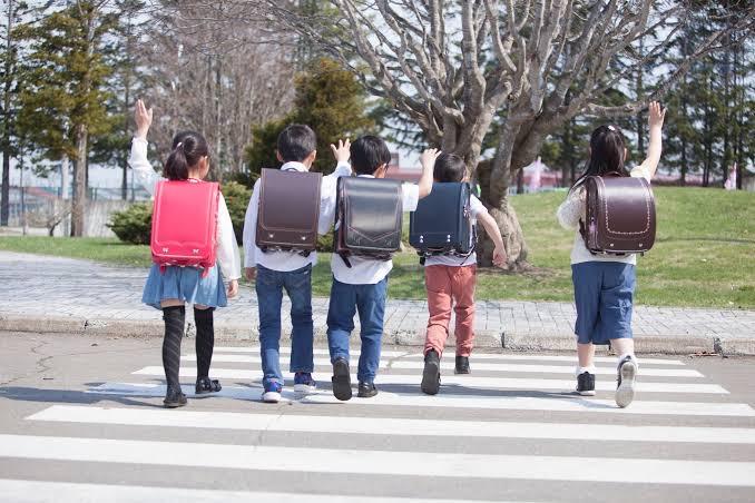 Trẻ em học sinh tiểu học Nhật Bản đeo cặp chống gù lưng